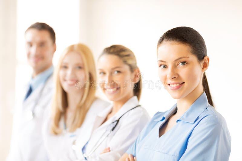 在医疗小组前面的女性医生 图库摄影