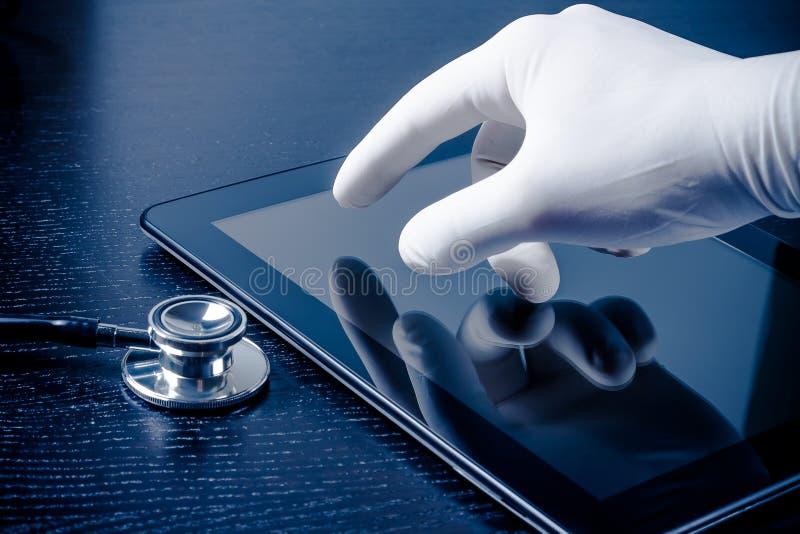 在医疗手套感人的现代数字式片剂个人计算机的手在听诊器附近 库存照片