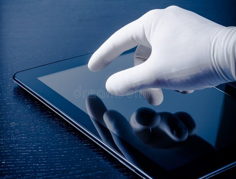在医疗手套感人的现代数字式片剂个人计算机的手 库存图片