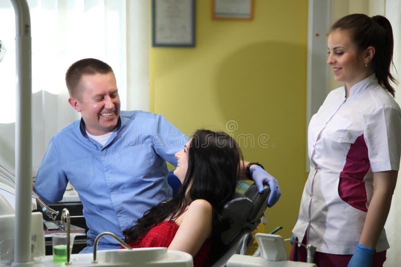 在治疗以后的愉快的少妇和男性牙医在诊所 免版税库存图片
