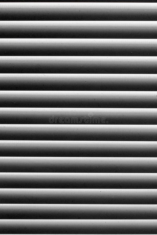 在黑白抽象条纹图形的图表纹理 在窗口的窗帘与在轻的小条的尘土 免版税库存图片