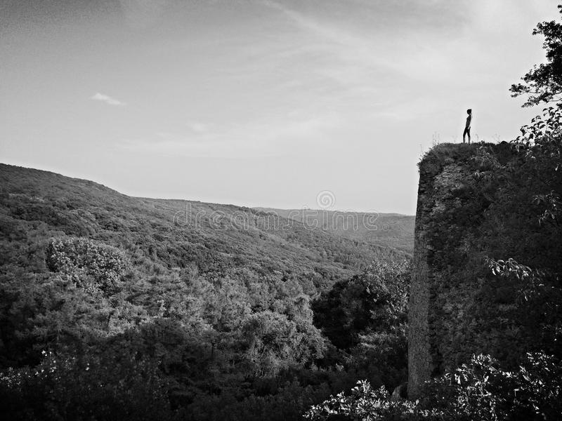在黑白的岩石的一个妇女立场 库存图片