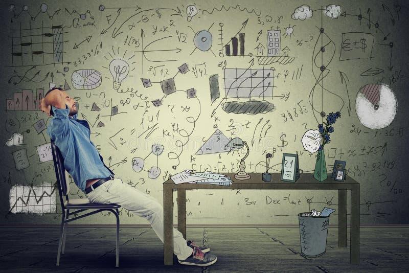 在他的办公室供以人员放松在他的书桌的企业家 库存照片