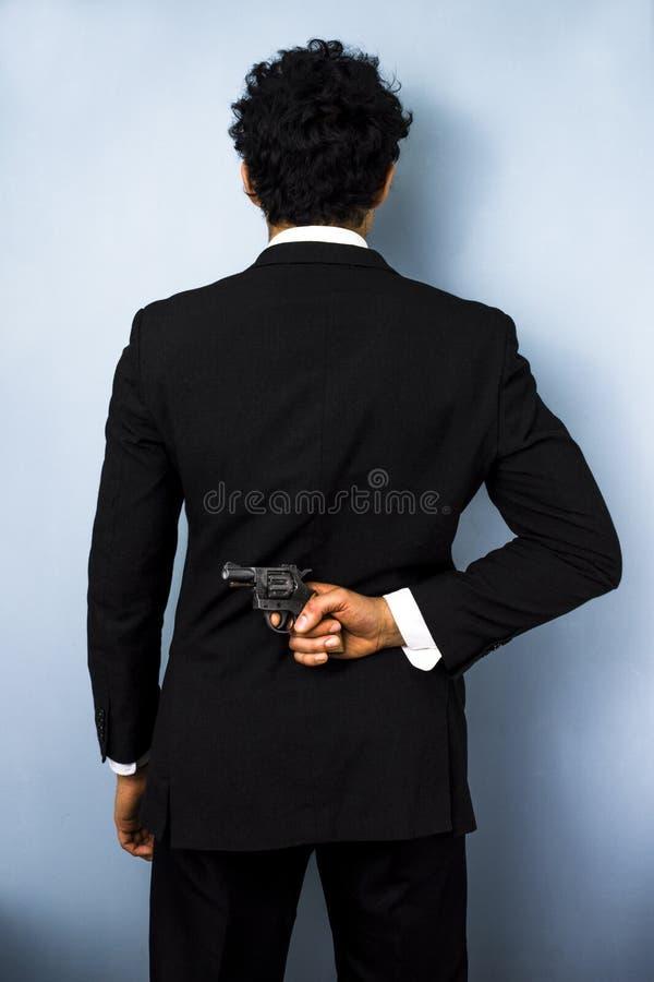 在他的后的商人掩藏的枪  免版税库存图片