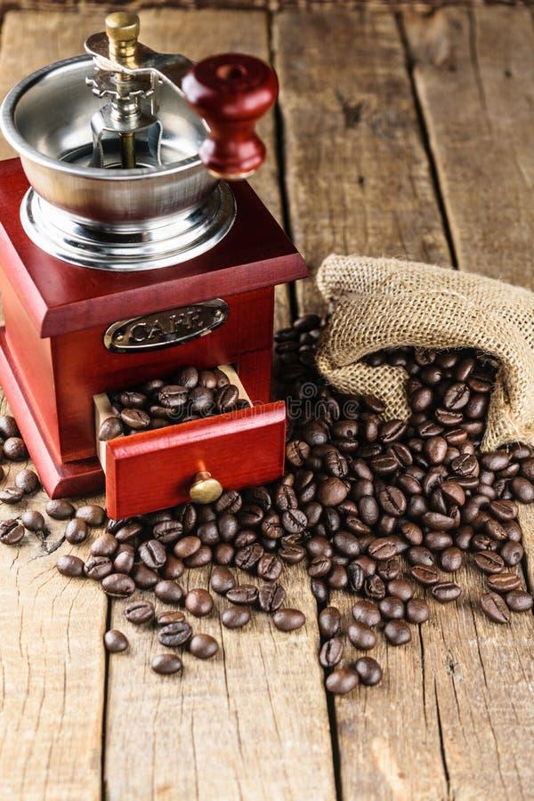在黄麻的咖啡豆请求与在木头的磨咖啡器 库存图片