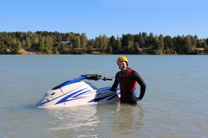 在他的喷气机滑雪附近的年轻人 图库摄影