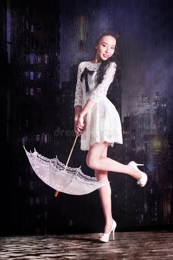 在轻的夏天礼服的年轻亭亭玉立的模型有摆在演播室的一把金银细丝工的伞的 黑色背景 库存照片