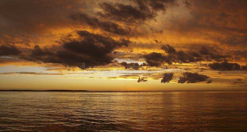 在水的多彩多姿的金黄日出 免版税库存图片