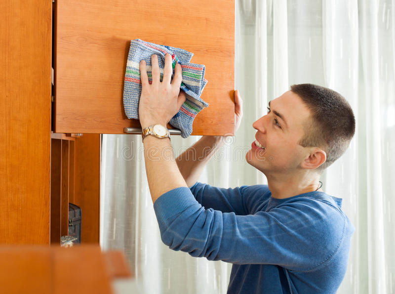 在他的客厅的愉快的人打扫灰尘家具 免版税库存照片