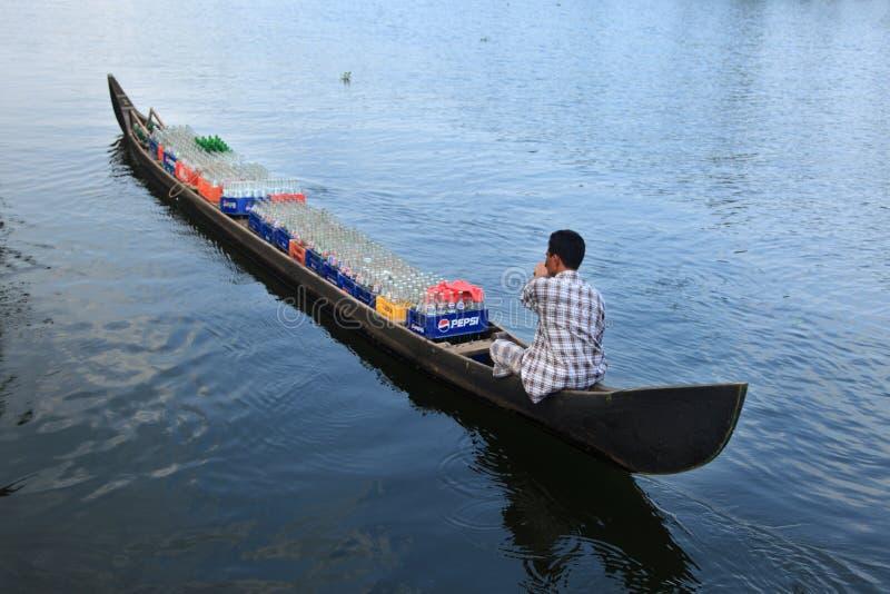 在他的小船的小船人运输软饮料瓶 免版税库存图片