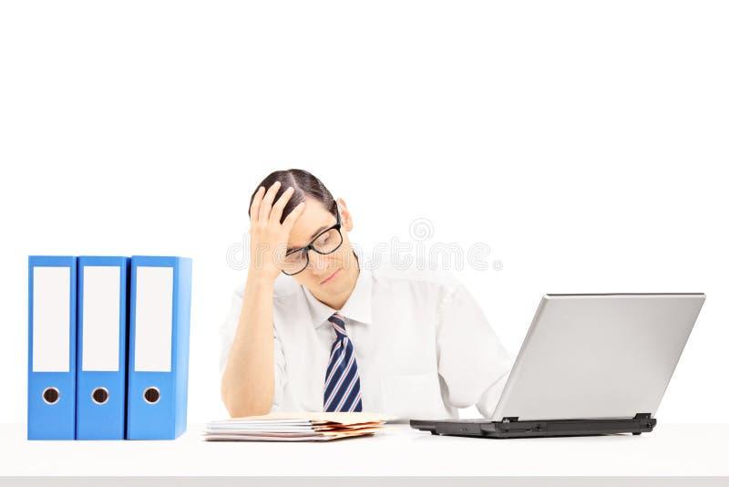 在他的工作场所的失望的年轻商人 免版税库存图片