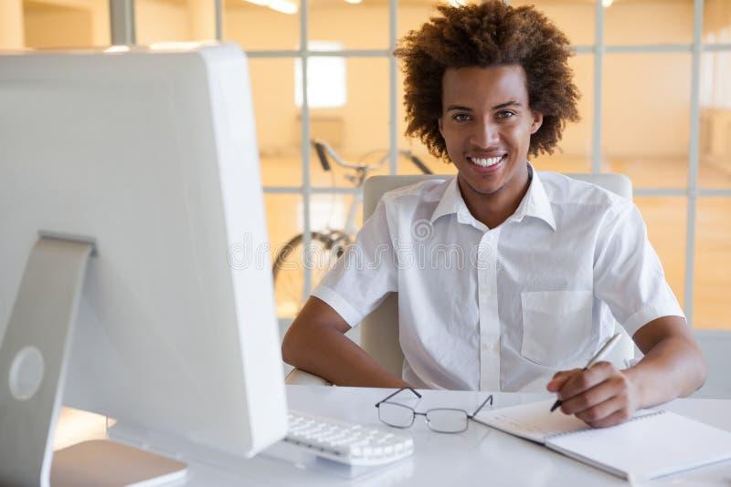 在他的微笑对照相机的书桌的偶然年轻商人文字 库存图片