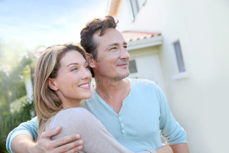 在他们的房子前面的愉快的夫妇 免版税库存照片