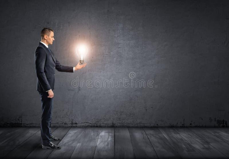 在他的手上的商人侧视图站立和拿着发光的电灯泡 图库摄影