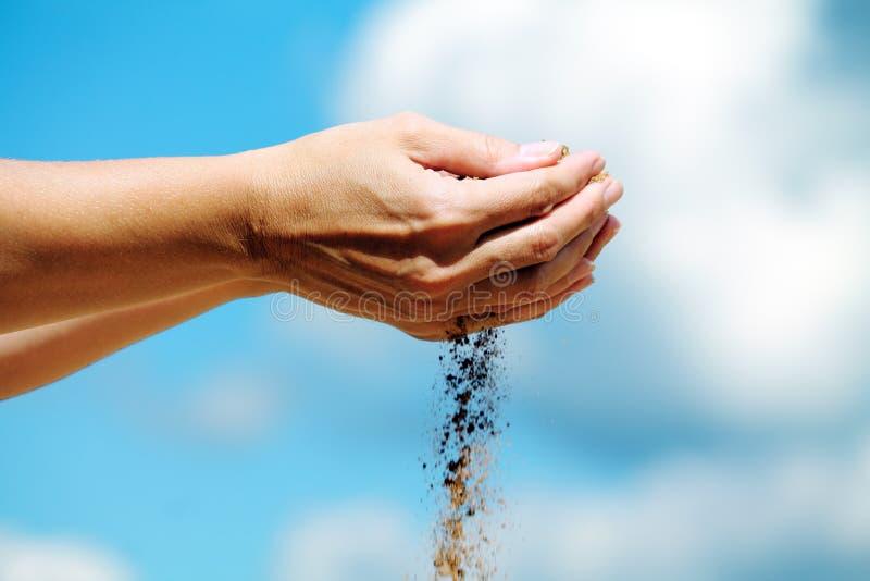 在他的手上的沙子 免版税库存图片