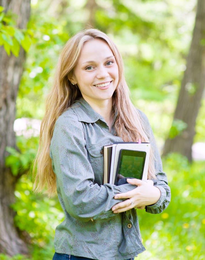 在他们的手上的美丽的女孩画象拿着书 免版税库存照片