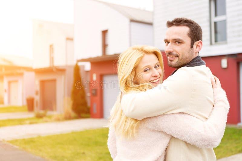 在他们的新房前面的年轻愉快的夫妇 库存图片