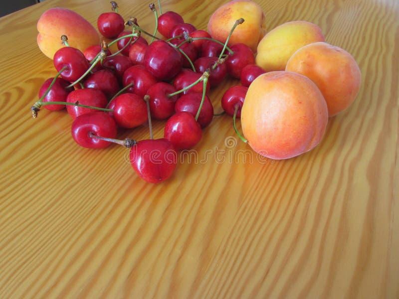 在轻的木桌上的新鲜的夏天果子 杏子和樱桃在木背景 免版税库存图片
