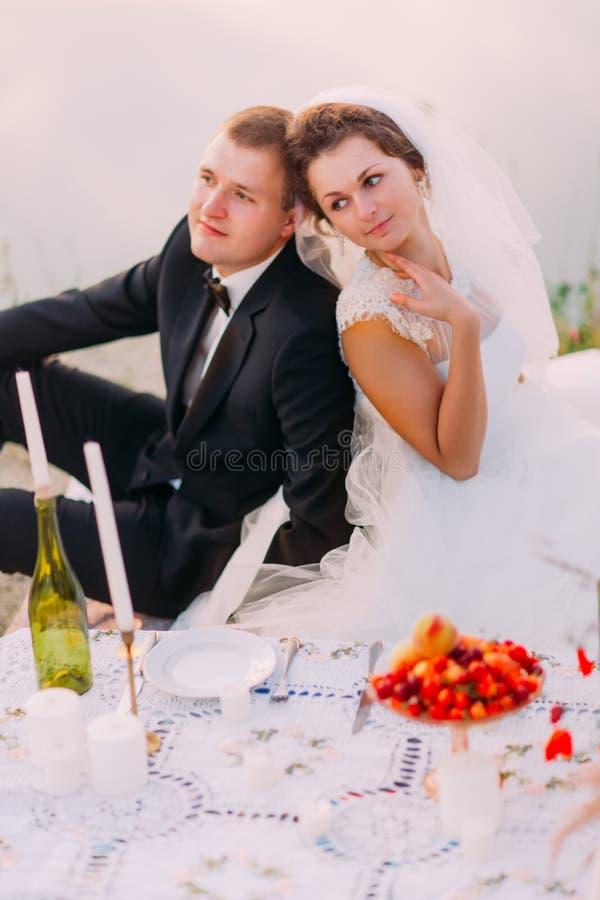 在他们的浪漫野餐期间,新娘紧接坐给新郎 在海的背景的特写镜头画象 免版税库存照片