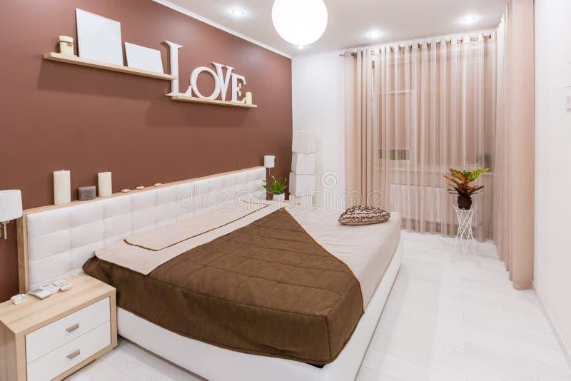 在轻的温暖的口气的现代简单派样式卧室内部 免版税库存照片
