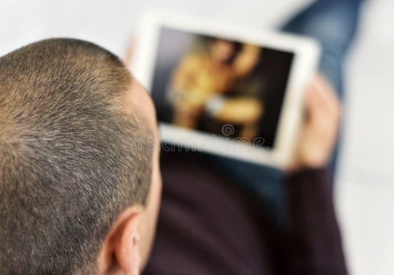 年轻在他的片剂的人观看的色情 免版税库存图片