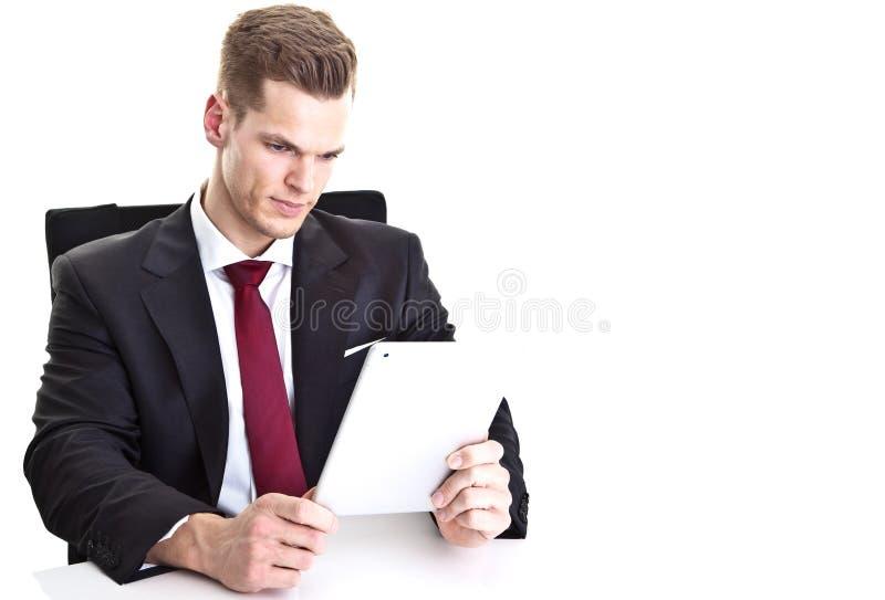 在他的现代片剂计算机/touchp上的年轻商人读书 免版税库存照片