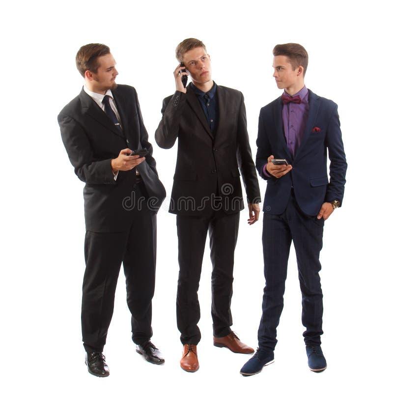 在他们的电话的三个商人 免版税库存图片