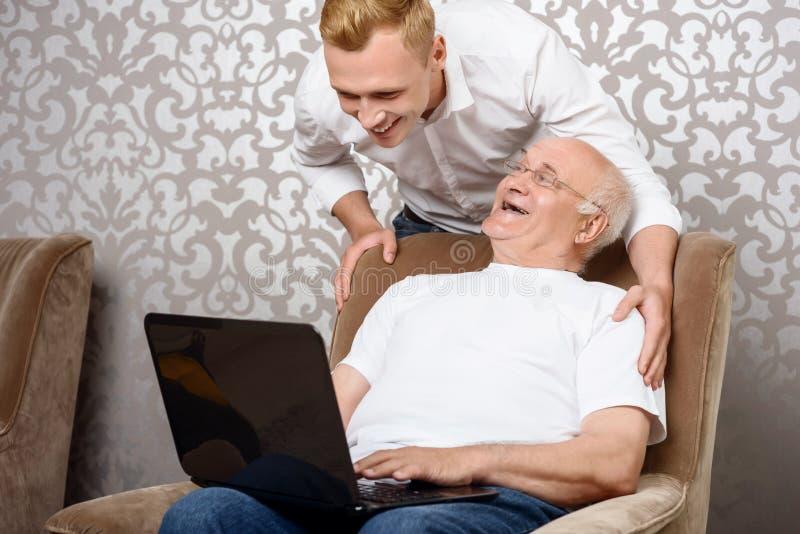 在他的祖父后的孙子有膝上型计算机的 免版税库存图片