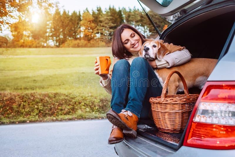 在他们的秋天汽车trav期间,有她的狗的妇女有茶时间 免版税库存照片