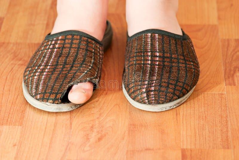 在他的脚的褴褛拖鞋 免版税库存照片
