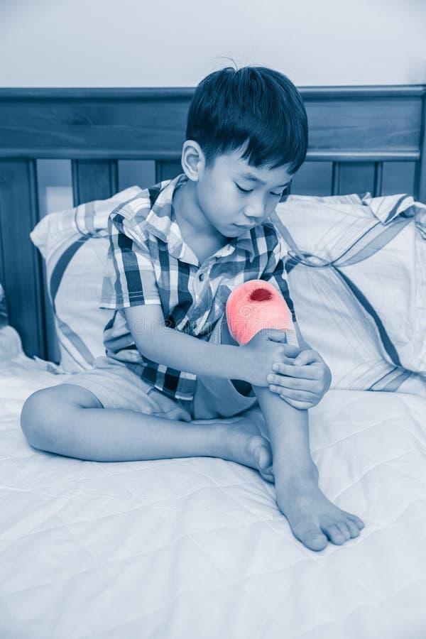 在他的膝盖伤害的孩子 孩子是事故 免版税库存图片