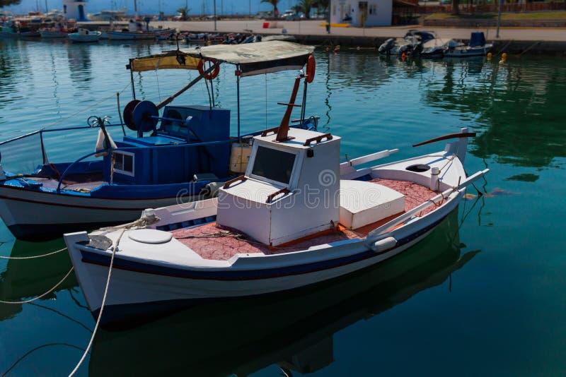 在水的被日光照射了白色,蓝色和红色地中海渔船在优卑亚岛- Nea Artaki,希腊 库存图片