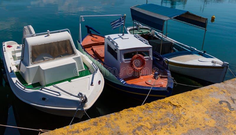 在水的被日光照射了红色,白色,绿色和蓝色地中海渔船在优卑亚岛- Nea Artaki,希腊 免版税图库摄影