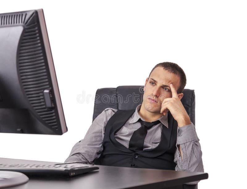 在他的计算机前面的疲乏的商人 免版税库存照片