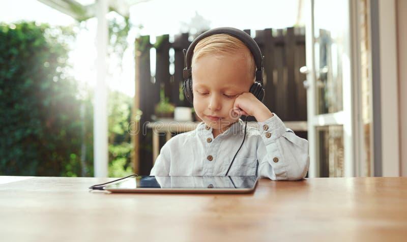 在他的音乐浸没的逗人喜爱的年轻男孩 免版税库存图片