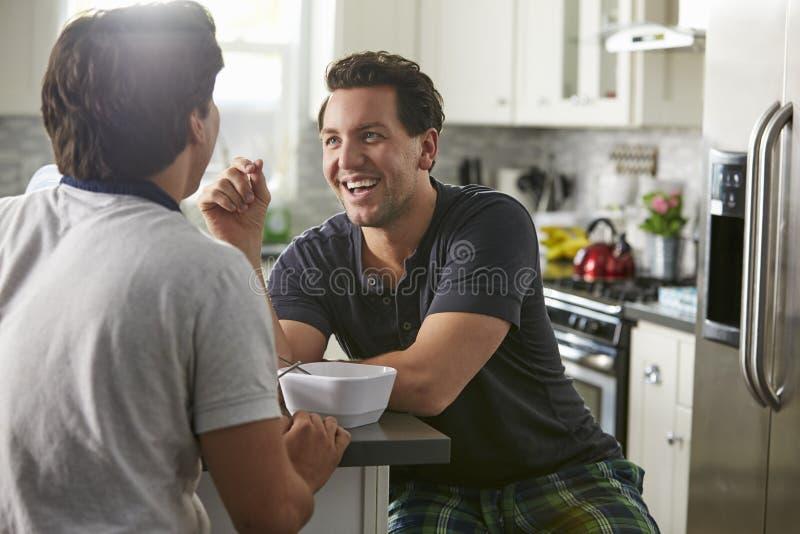 在他们的20s的男性快乐夫妇在他们的厨房,关闭里谈话  免版税图库摄影