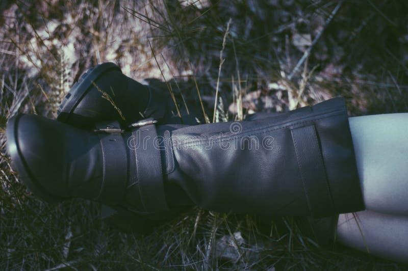 在黑皮靴的妇女腿在草和秋叶 对 图库摄影