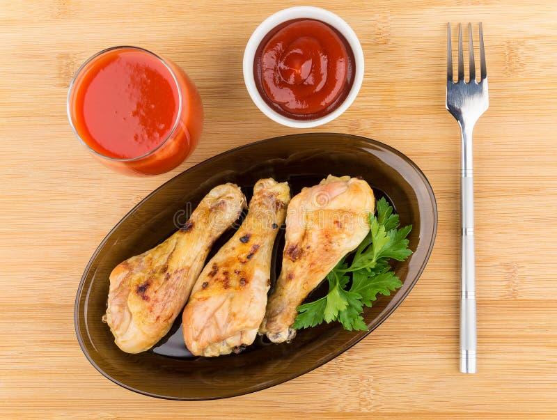 在黑盘、西红柿汁和调味汁的炸鸡腿 库存图片
