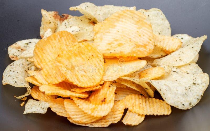 在黑盘的土豆片 免版税库存照片