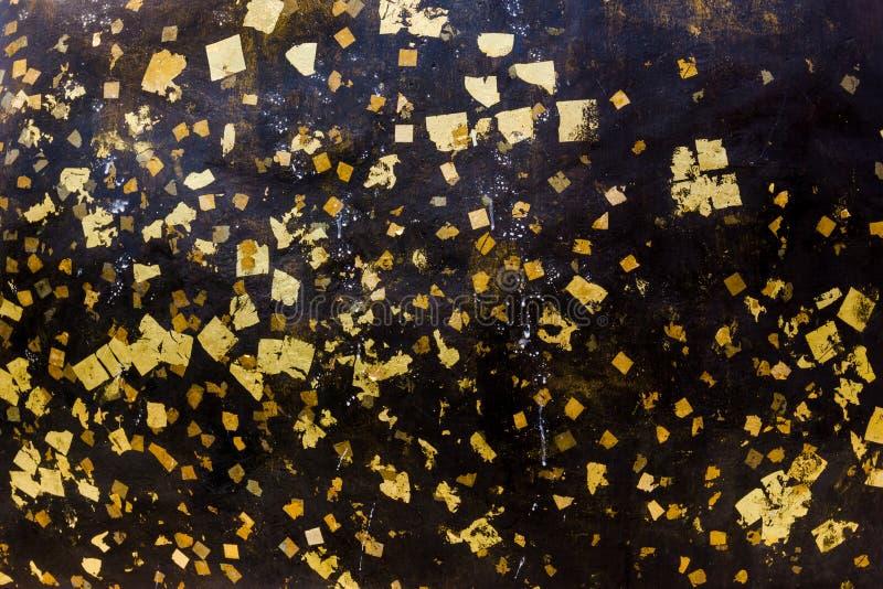 在黑石墙上的金叶 图库摄影