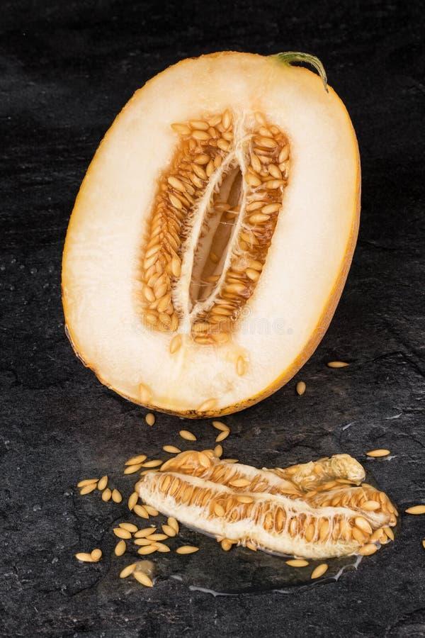 在黑石背景的一个成熟和未加工的瓜 甜瓜瓜切成了两半 水多的瓜honedew 甜和鲜美果子 库存图片