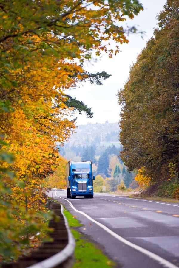 在绕秋天路的蓝色经典现代半卡车 库存图片