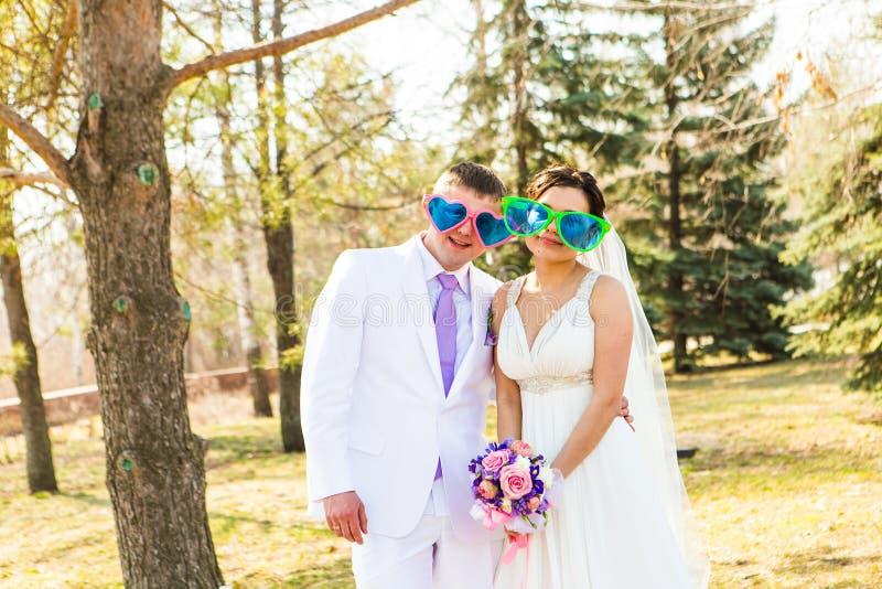 在滑稽的大玻璃的年轻婚礼夫妇 库存照片