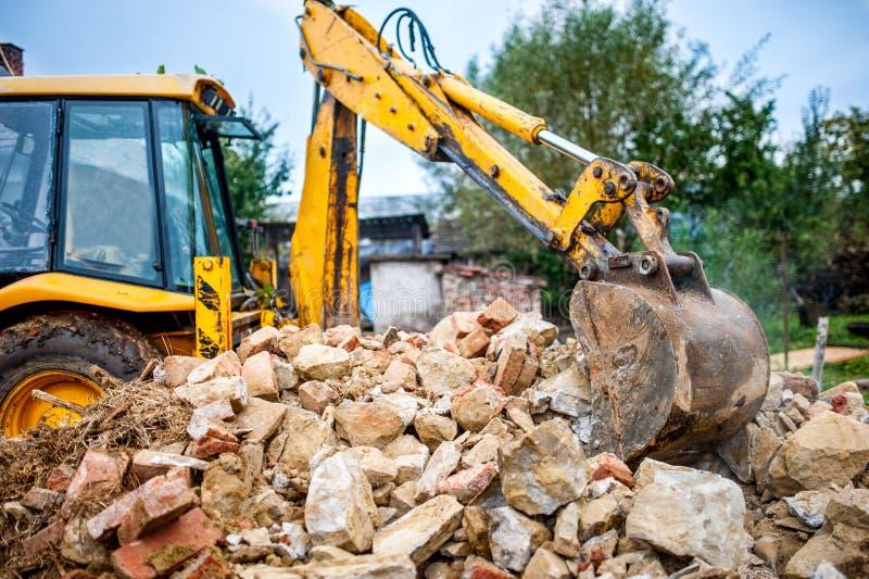 在建筑和爆破位置的工业水力挖掘机,回收与推土机的建筑废物 免版税库存照片
