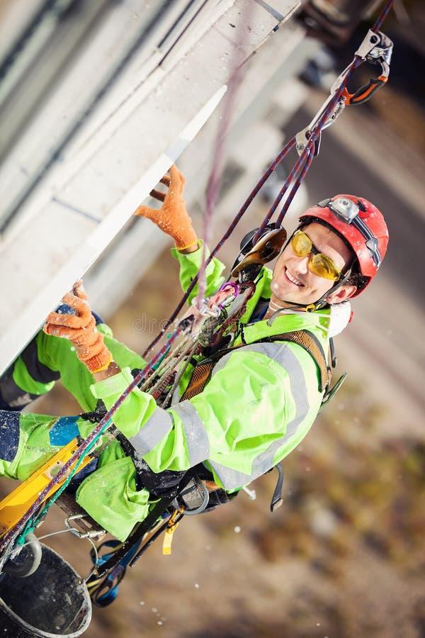 在绝缘材料工作期间的工业登山人 库存照片