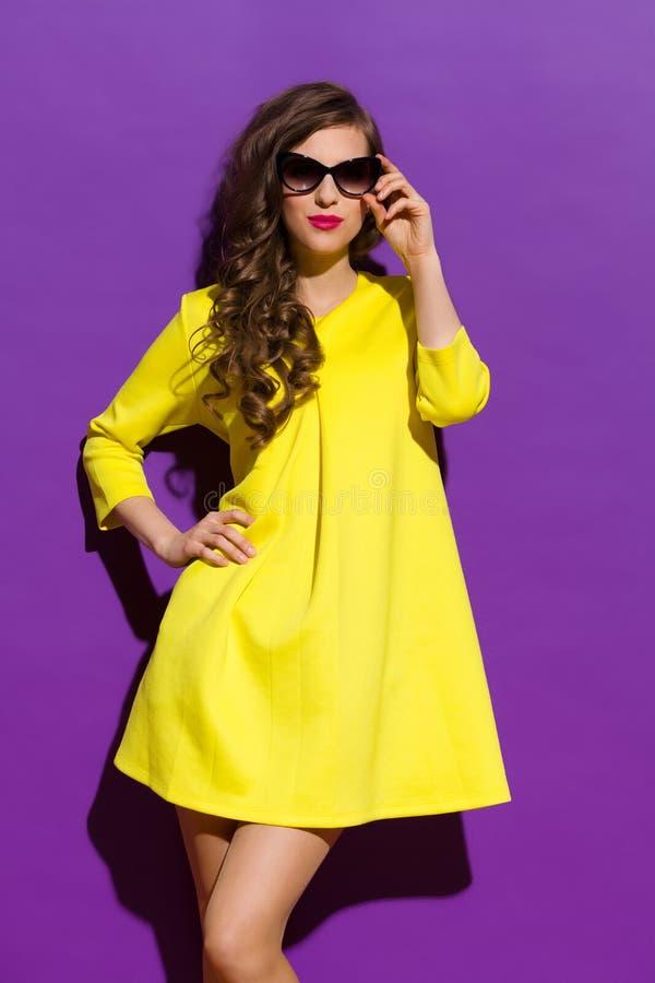 在紫罗兰色背景的黄色礼服 免版税库存照片