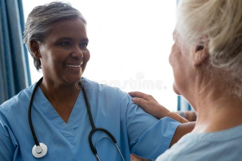 在养老院护理谈话与资深患者 免版税库存图片