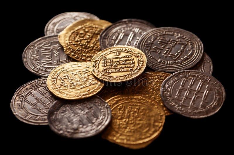 在黑背景的古老伊斯兰教的金黄和银币 免版税库存照片