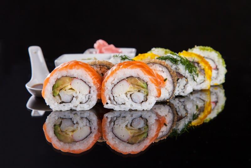 在黑背景的可口寿司片 免版税库存图片