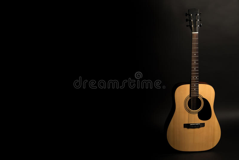 在黑背景的声学吉他在框架的右边 弦乐器 水平的框架 库存图片